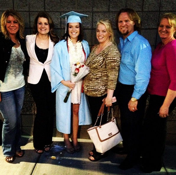 Madison Brown poses with her father and four mothers on her graduation day.